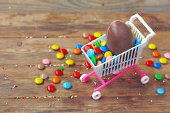 Easter chocolate egg, colorful candy on wooden table. Easter sale concept stock photo
