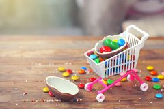 Easter chocolate egg, colorful candy on wooden table. Easter sale concept royalty free stock photo