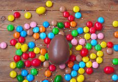 Easter chocolate egg, colorful candy on wooden table top view royalty free stock photography