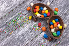 Easter chocolate egg with colorful explosion of candies and sweets on gray colored wooden background. Stock Photos