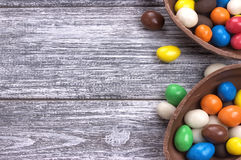 Easter chocolate egg with colorful explosion of candies and sweets on gray colored wooden background. Stock Image