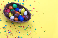 Easter chocolate egg with colorful explosion of candies and sweets on yellow colored background. Royalty Free Stock Images