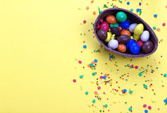 Easter chocolate egg with colorful explosion of candies and sweets on yellow colored background. Royalty Free Stock Image