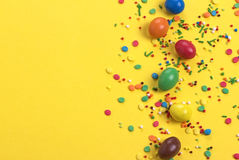 Easter chocolate egg with colorful explosion of candies and sweets on yellow colored background. Royalty Free Stock Photos