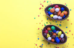 Easter chocolate egg with colorful explosion of candies and sweets on yellow colored background. Royalty Free Stock Photo