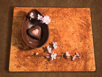 Easter chocolate egg with a surprise of a decorated heart,sprinkled with cocoa powder,chocolate chips and almond blossom. Stock Image