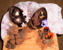 Easter chocolate egg with a surprise of two hearts decorated and an easter rabbit,sprinkled with cocoa powder and spring flowers. Royalty Free Stock Image