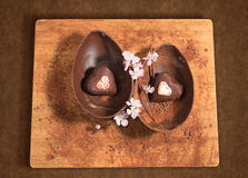 Easter chocolate egg with a surprise of two hearts decorated,sprinkled with cocoa powder and almond blossom. Stock Images