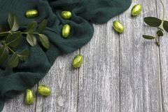 Easter chocolate eggs in foil with green fabric on gray wooden background. Easter chocolate eggs in foil with green fabric on gray wooden background Royalty Free Stock Images