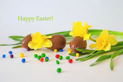 Easter chocolate eggs and fresh spring daffodils on weathered white background. copy space - Happy Easter royalty free stock photo