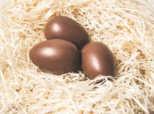 Easter. Chocolate eggs lie in a nest on a wooden white table stock images
