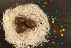 Easter. Chocolate eggs with multicolored candies lie in a nest on a wooden white table royalty free stock photography