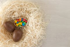 Easter. Chocolate eggs with multicolored candies lie in a nest on a wooden white table royalty free stock photos