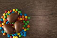 Easter. Chocolate eggs with multicolored candies lie on a wooden brown table stock images