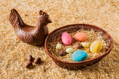 Easter chocolate eggs over the straw. Easter chocolate chicken over the straw and some eggs in a basket royalty free stock photos