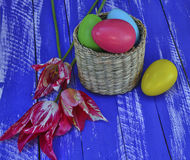Easter chocolate eggs in a wicker basket on a wooden background Royalty Free Stock Photo