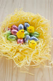 Easter chocolate eggs nest with yellow chickens. Easter chocolate eggs, wrapped in shiny colorful foil, placed in a nest made of yellow, shredded tissue paper stock images