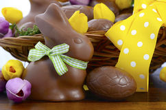 Easter chocolate hamper of eggs and bunny rabbits. Happy Easter chocolate hamper of eggs and bunny rabbits in large basket with yellow and pink purple silk tulip Stock Images