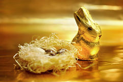 Easter chocolate rabbit and eggs on gold background Royalty Free Stock Images