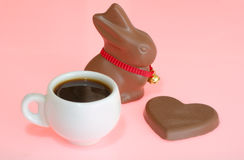 Easter chocolates and espresso. Easter chocolates - bunny and heart -  with espresso on pink background Royalty Free Stock Image