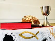 Easter christian celebration symbols. Open Bible with bread, caliche, and cross in background for communion celebration stock photography