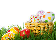 Easter color eggs in basket on green grass Stock Photos