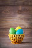 Easter color eggs in basket on wood Royalty Free Stock Photos