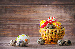 Easter color eggs in basket on wood Royalty Free Stock Photography