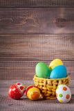Easter color eggs in basket on wood Royalty Free Stock Images
