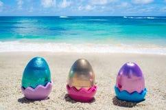 Easter color eggs on the beach near ocean Stock Photos