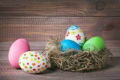 Easter color eggs in nest on wood Stock Images