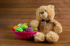 Easter color painted eggs in basket and teddy bear Royalty Free Stock Photos
