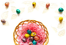 Easter color quail eggs on a white background,leaves cut from p. Happy easter background, color quail eggs on white paper, the leaves are cut from paper and Stock Image