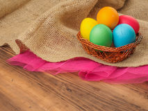 Easter colored egg in a wicker-work from withe basket. Mock up for your greetings card, poster or other design. Russian Royalty Free Stock Photography