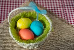Easter colored eggs in a basket on a canvas napkin and checkered tablecloth stock images