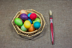 Easter colored eggs in basket on dark green rough cotton texture Stock Image