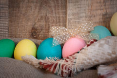 Easter colored eggs with bow against natural wooden textured background on linen fabric. Royalty Free Stock Photography
