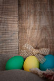 Easter colored eggs with bow against natural wooden textured background on linen fabric. Stock Photo