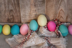 Easter colored eggs with bow against natural wooden textured background Royalty Free Stock Photos