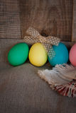 Easter colored eggs with bow against natural wooden textured background Stock Photography