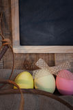 Easter colored eggs with bow and black board with copy space for text against natural wooden textured background on linen fabric. Stock Image