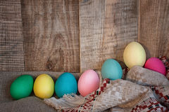Easter colored eggs with bow and black board with copy space for text against natural wooden textured background on linen fabric. Stock Images
