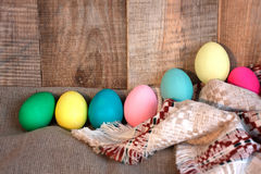 Easter colored eggs with bow and black board with copy space for text against natural wooden textured background on linen fabric. Stock Photo