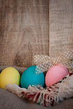 Easter colored eggs with bow and black board with copy space for text against natural wooden textured background on linen fabric. Royalty Free Stock Photos