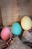 Easter colored eggs with bow and black board with copy space for text against natural wooden textured background on linen fabric. Royalty Free Stock Image