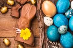 Easter eggs on rustic wood background text space. Easter holiday card. Easter colored eggs, chocolate bunnies and sweets on rustic wooden background, easter Stock Photography