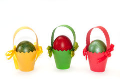 Easter colored eggs in colored carton baskets Royalty Free Stock Photos