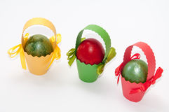 Easter colored eggs in colored carton baskets Stock Photo