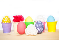 Easter colored eggs in colorful buckets and paper flowers Stock Photos