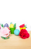 Easter colored eggs in colorful buckets and paper flowers Stock Image